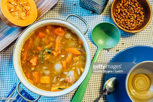 high angle view of pumpkin soup in cooking pan on table - ladle stock photos and pictures