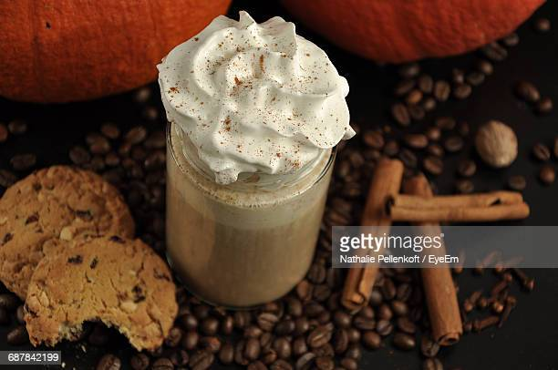 High Angle View Of Pumpkin Spice Latte And Roasted Coffee Beans On Table