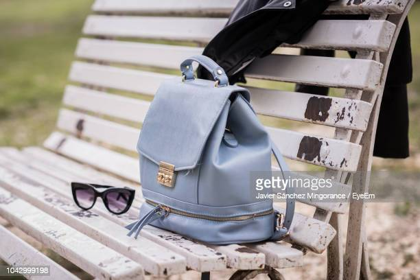 high angle view of purse with sunglasses and leather jacket on bench - giacca di pelle foto e immagini stock