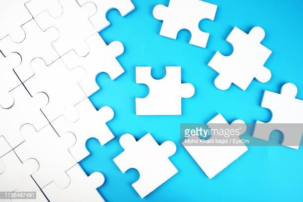high angle view of puzzle pieces on blue background - jigsaw piece stock pictures, royalty-free photos & images