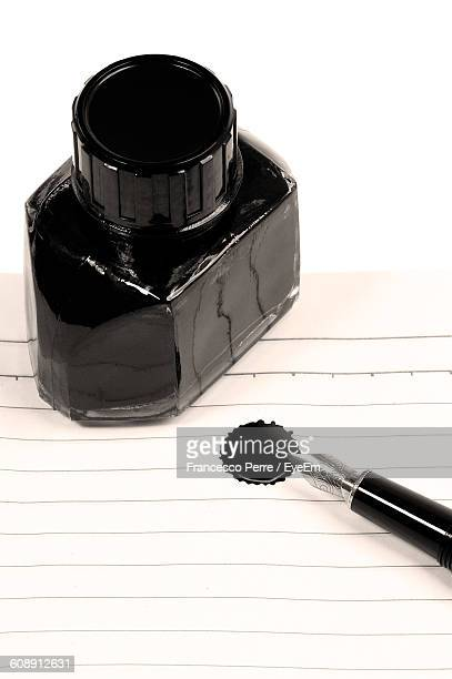 High Angle View Of Quill Pen And Inkwell On Paper Against White Background