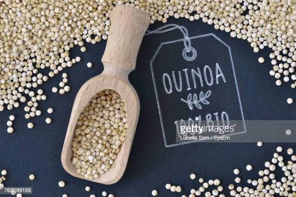 high angle view of quinoa with wooden spoon on board - quinoa stock pictures, royalty-free photos & images