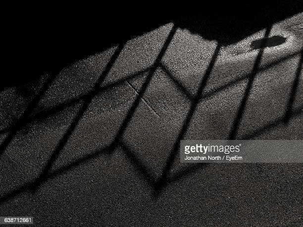 High Angle View Of Railing Shadow On Street At Night