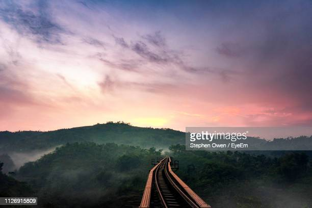 high angle view of railroad track against sky during sunset - bahngleis stock-fotos und bilder