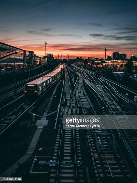 high angle view of railroad tracks against sky during sunset - bahngleis stock-fotos und bilder