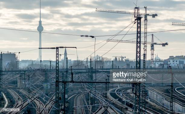 high angle view of railroad tracks with fernsehturm in background against cloudy sky - bahngleis stock-fotos und bilder