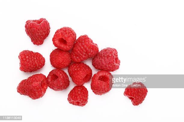 high angle view of raspberries on white background - berry fruit stock pictures, royalty-free photos & images