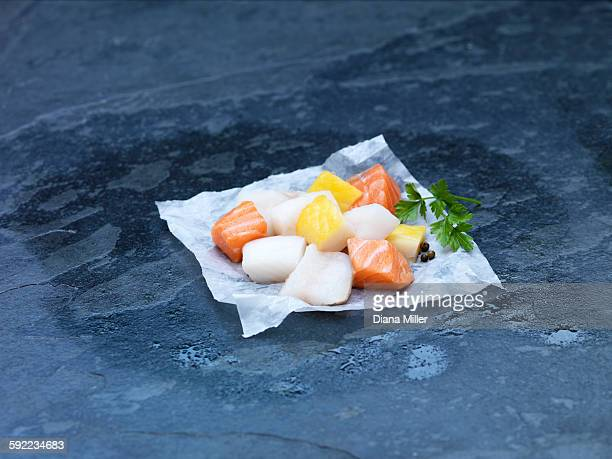 High angle view of raw cubed salmon, cod and herbs for making fish pie