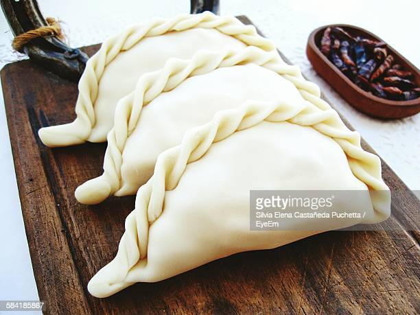High Angle View Of Raw Empanadas On Wooden Plate