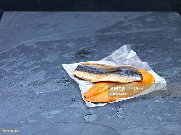 High angle view of raw Scottish kipper fillets on baking paper and slate