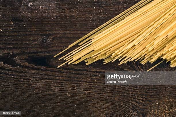 High Angle View Of Raw Spaghetti On Wooden Table