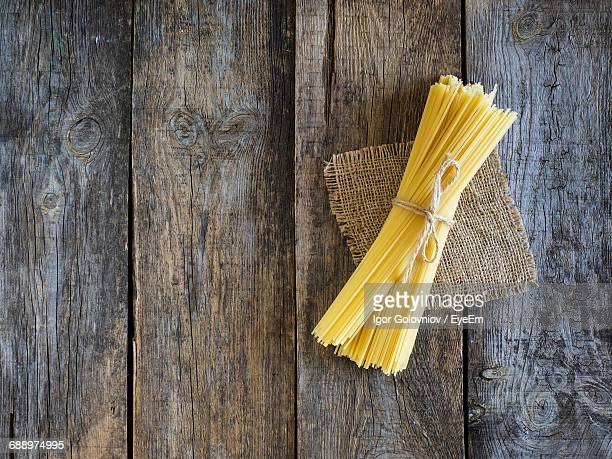 high angle view of raw spaghetti on wooden table - igor golovniov stock pictures, royalty-free photos & images