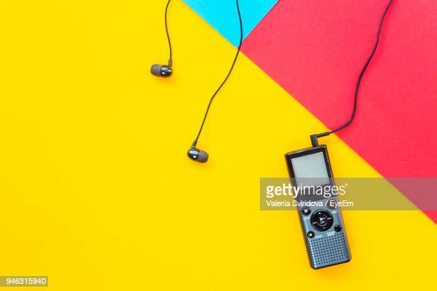 high angle view of recorder with headphones on colored background - recorder musical instrument stock photos and pictures