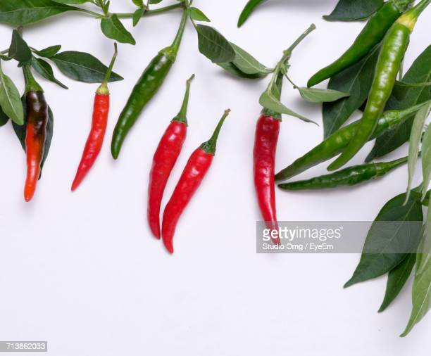 High Angle View Of Red And Green Chili Peppers With Leaves On White Background