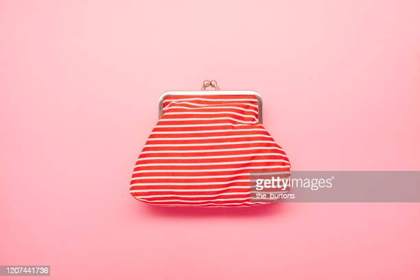 high angle view of red and white striped wallet on pink colored background - handbag stock pictures, royalty-free photos & images