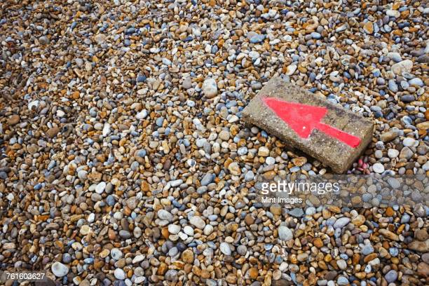 High angle view of red arrow painted on stone lying on pebble beach.