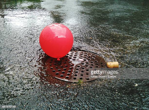 High Angle View Of Red Balloon On Wet Manhole