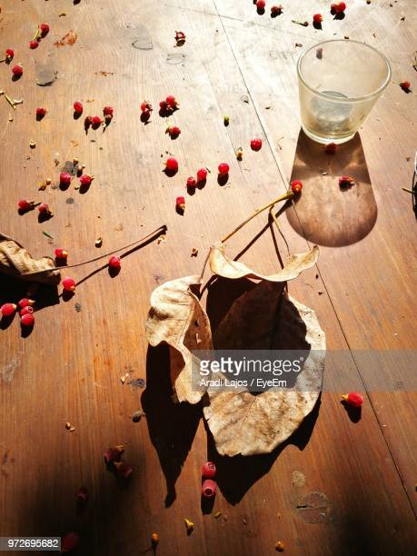 High Angle View Of Red Berries With Dry Leaves On Wooden Table