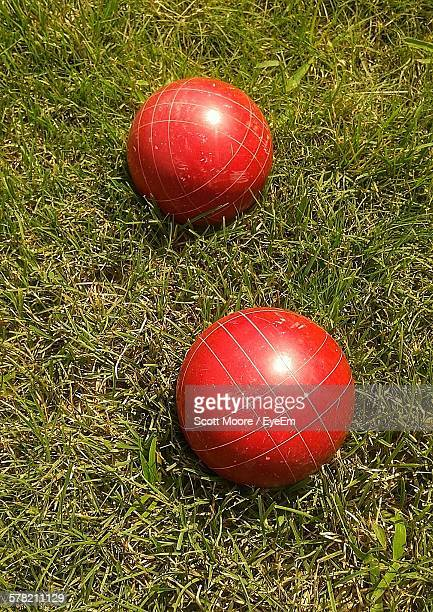 High Angle View Of Red Bocce Balls On Grass In Park