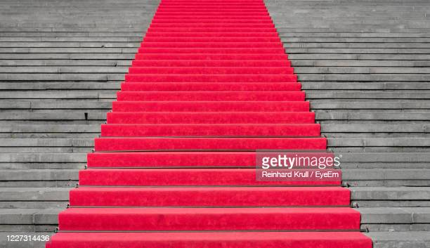 high angle view of red carpet on stairs - red carpet event stockfoto's en -beelden