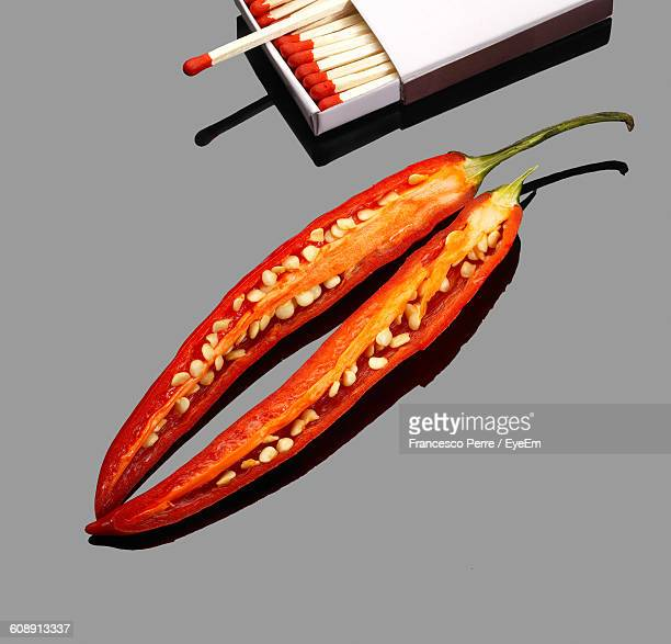 High Angle View Of Red Chili Pepper With Matchbox On Gray Background