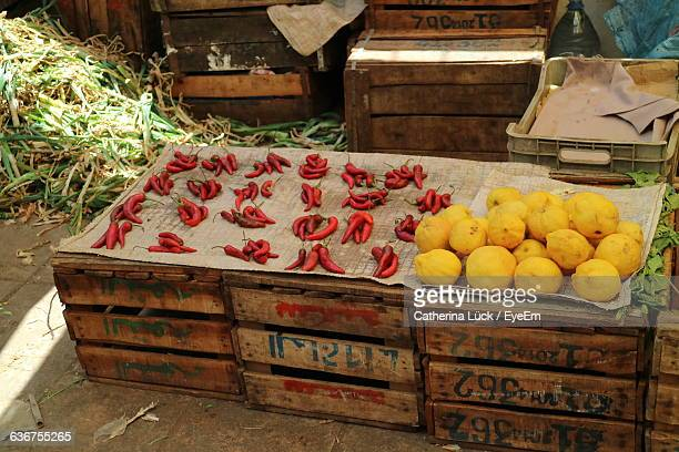 High Angle View Of Red Chili Peppers And Lemons On Crates At Market Stall