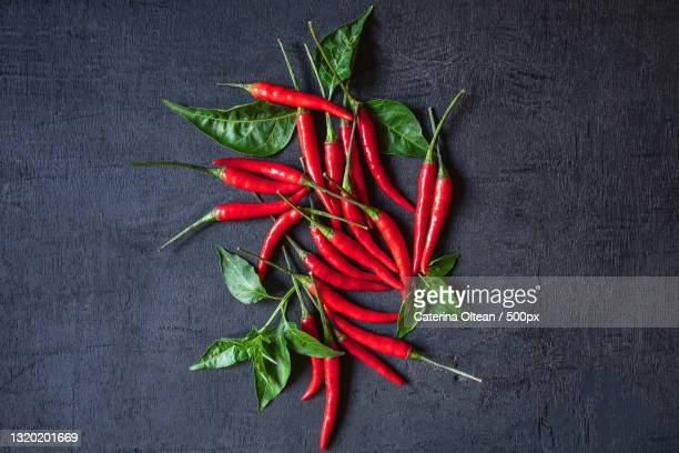 high angle view of red chili peppers on table - red chili pepper stock pictures, royalty-free photos & images