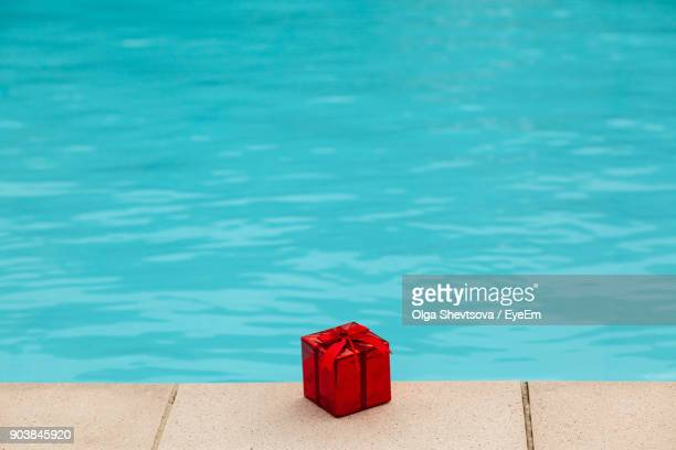 High Angle View Of Red Christmas Present At Poolside