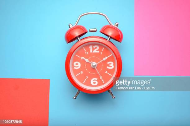High Angle View Of Red Clock Against Colored Background