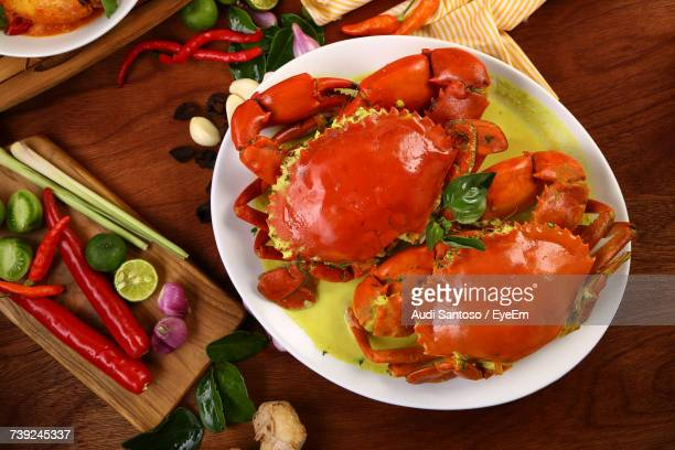 high angle view of red crabs with sauce in plate by ingredients on table - chilli crab stock photos and pictures