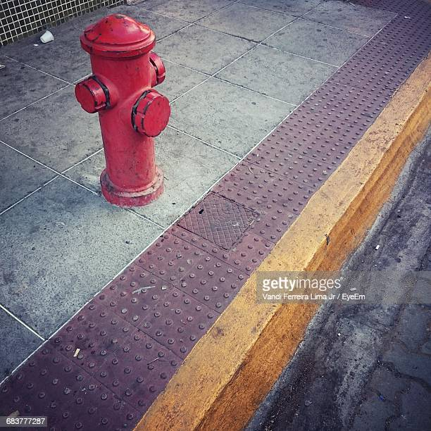 High Angle View Of Red Fire Hydrant On Footpath
