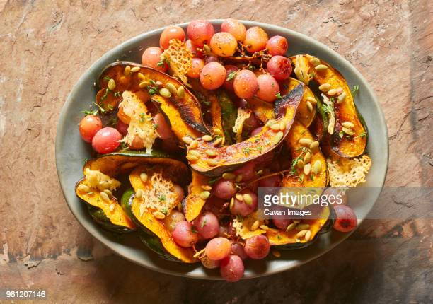 High angle view of red grapes with acorn squash in plate on table