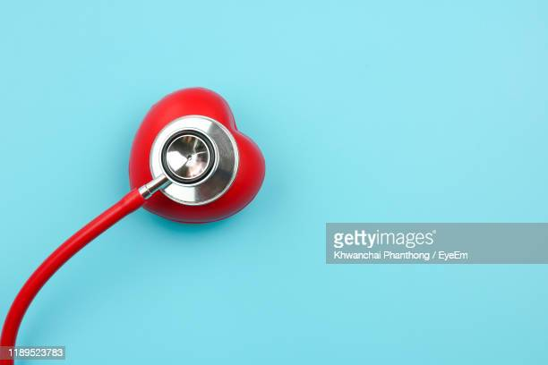 high angle view of red heart model with stethoscope over blue background - heart health stock pictures, royalty-free photos & images