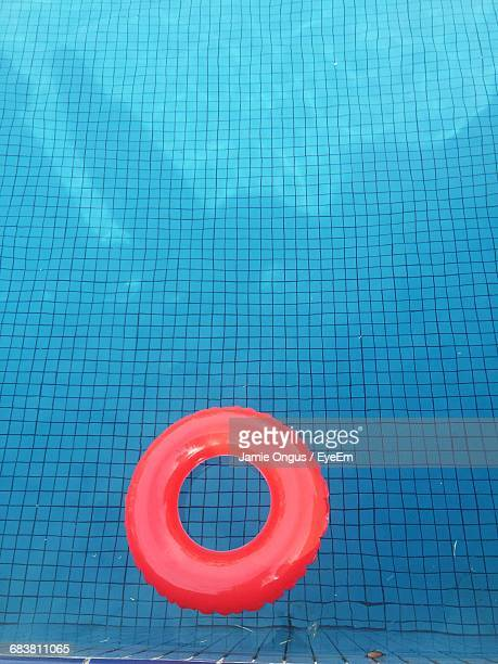 high angle view of red inflatable ring floating on swimming pool - vertical red tube fotografías e imágenes de stock
