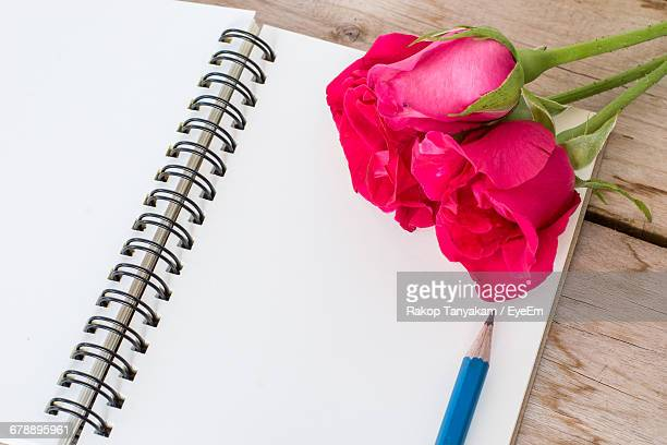High Angle View Of Red Rose By Pencil On Spiral Notebook