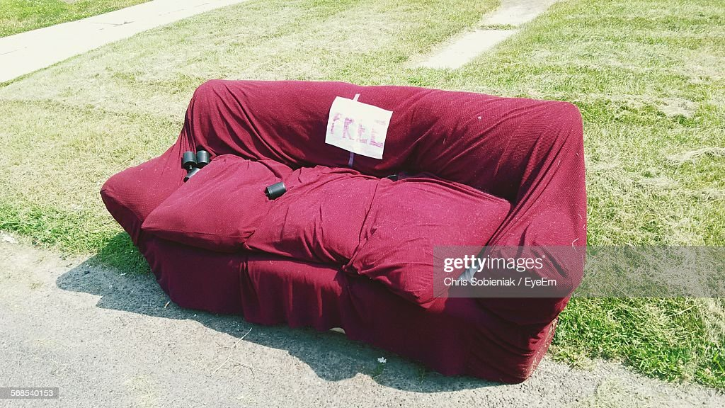 High Angle View Of Red Sofa On Grassy Field : Stock Photo