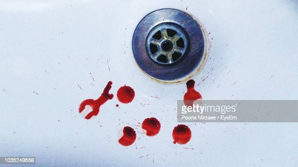 high angle view of red stains by drain in sink - blood in sink stock pictures, royalty-free photos & images