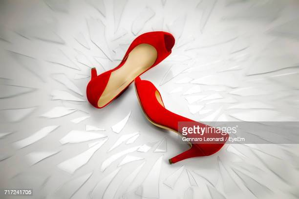 high angle view of red stilettos and glass pieces over white background - high heels stock pictures, royalty-free photos & images