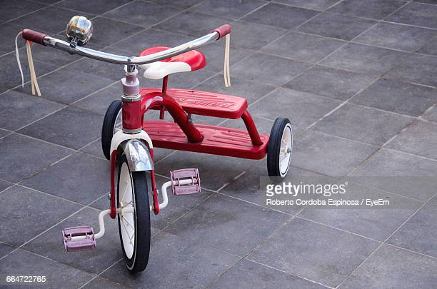 high angle view of red tricycle on tiled floor - tricycle stock pictures, royalty-free photos & images