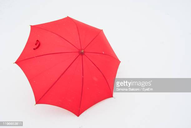 high angle view of red umbrella against white background - umbrella stock pictures, royalty-free photos & images