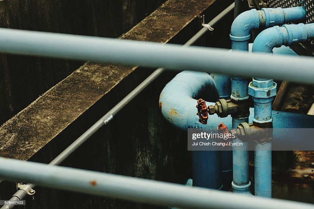 High Angle View Of Red Valves On Blue Metallic Pipes : Stock Photo