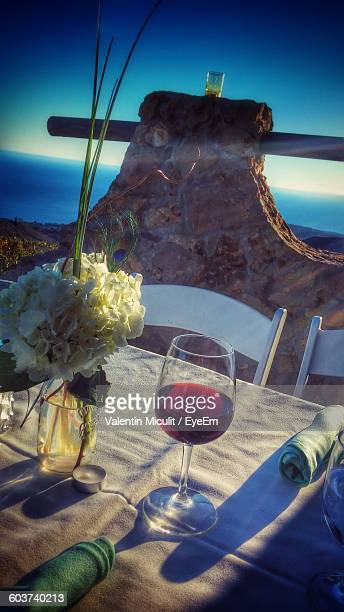 High Angle View Of Red Wine Glass By Flower Vase On Table In Restaurant