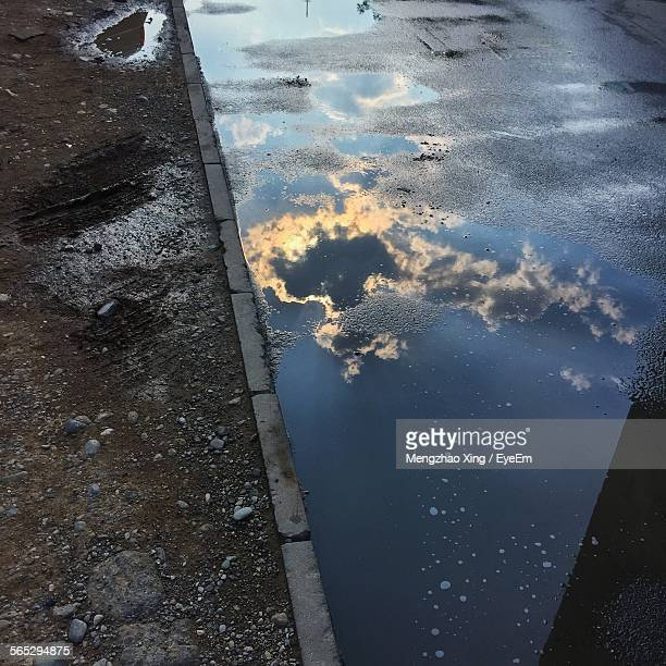 High Angle View Of Reflection In Puddle On Street