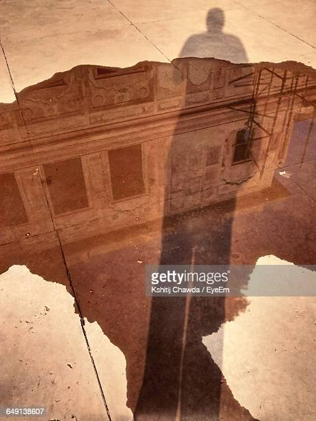 High Angle View Of Reflection In Puddle With Shadow On Footpath