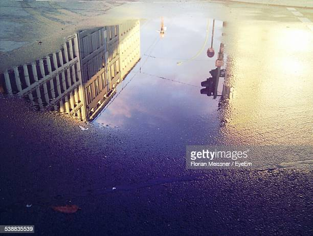 high angle view of reflection of building on puddle at street - spiegelung stock-fotos und bilder