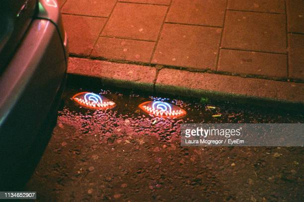 high angle view of reflection of neon lights on wet street - mcgregor stock pictures, royalty-free photos & images