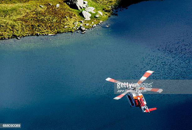 high angle view of rescue helicopter flying over lake at snowdonia national park - rescue stock pictures, royalty-free photos & images