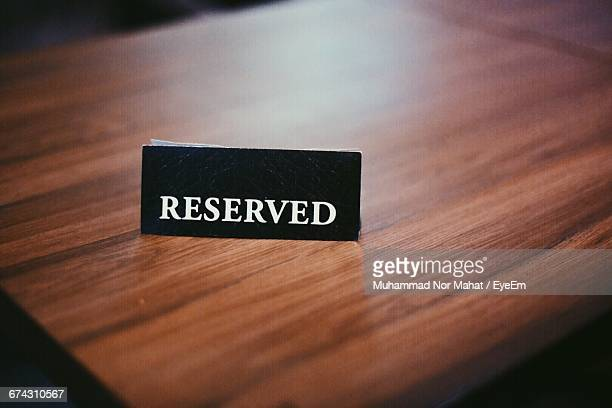 High Angle View Of Reserved Sign On Wooden Table