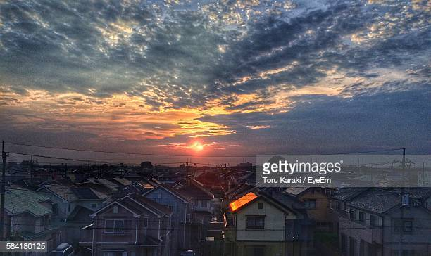 High Angle View Of Residential District Against Cloudy Sky During Sunset