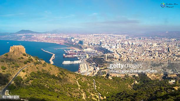 high angle view of residential district and sea against sky - oran algeria photos et images de collection